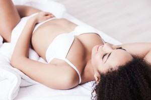Cheerful mulatto woman is relaxing in bed
