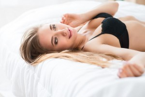 Sexually attractive girl lying in bed